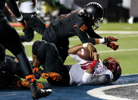 Rosenberg Terry quarterback Kishawn McClain (10) falls backward into the end zone as he is hit by Texas City's Allen Mull (5) during the second half of a Class 4A Bi-district high school playoff football game at Rice Stadium on Thursday, Nov. 14, 2013, in Houston. Photo: Brett Coomer, Houston Chronicle / © 2013  Houston Chronicle