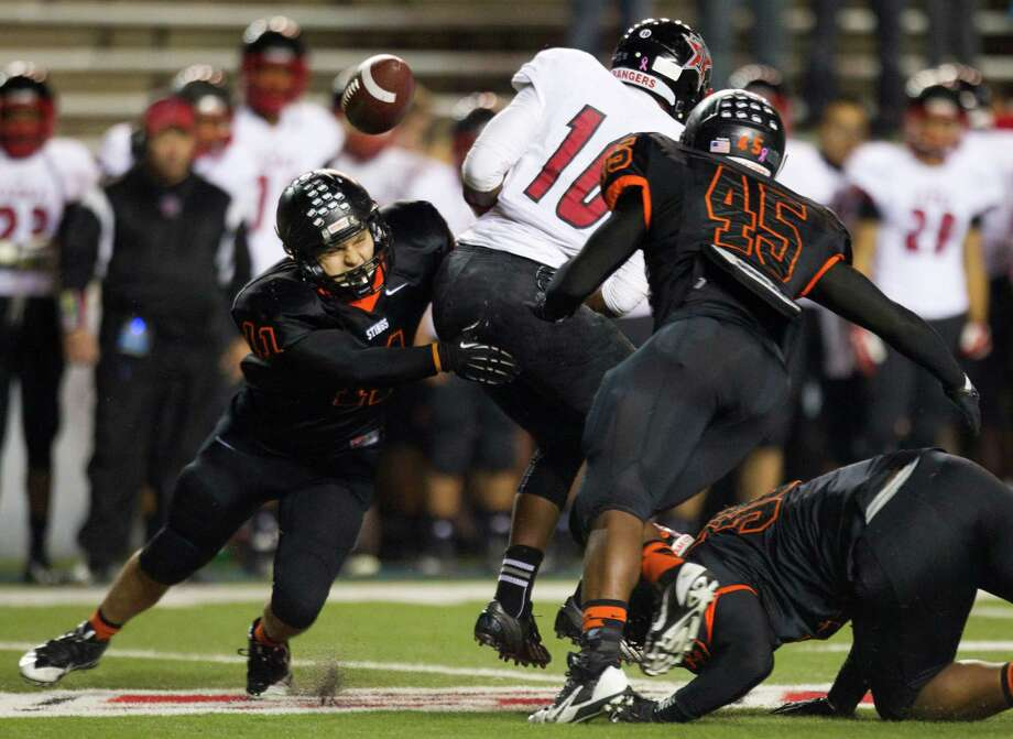 Texas City linebacker Cameron Moreno, left, forces a fumble by Terry quarterback Kishawn McClain (10) during the first half Thursday. Photo: Brett Coomer, Staff / © 2013  Houston Chronicle