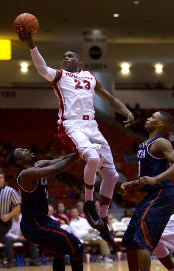 Houston Cougars guard Danuel House, center, jumps over University of Texas San Antonio Road Runners guard Keon Lewis, left and guard Devon Agusi, right, for a shot during the second half of their matchup in the Hofheinz Pavillion at the University of Houston, Thursday, Nov. 14, 2013, in Houston. Houston won 80-62. (Cody Duty / Houston Chronicle) Photo: Cody Duty, Houston Chronicle