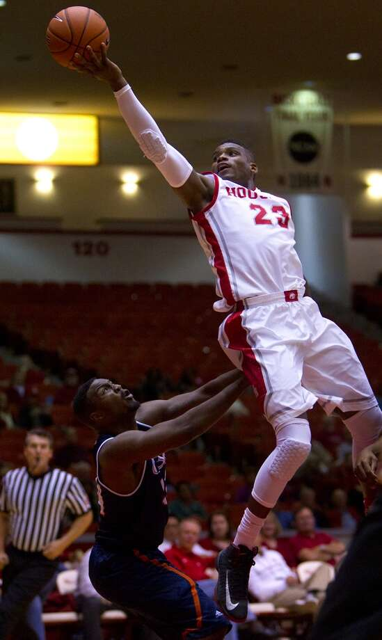 Houston Cougars guard Danuel House, center, jumps over University of Texas San Antonio Road Runners guard Keon Lewis, left, for a shot during the second half of their matchup in the Hofheinz Pavillion at the University of Houston, Thursday, Nov. 14, 2013, in Houston. Houston won 80-62. (Cody Duty / Houston Chronicle) Photo: Cody Duty, Houston Chronicle