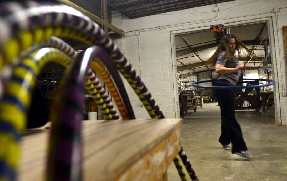 Alexandra Gillette warms up before she begins her weekly hula hoop class - featuring the water-weighted hula hoops in the foreground, which Gillette makes - at The Art Studio. Beth Rankin/cat5