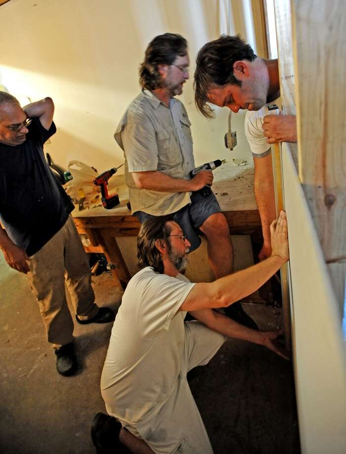 Greg Busceme, left, looks over as Joe Winston, top, John Fulbright, bottom, and Nathaniel Welch, right, work on setting dry wall during the first days of the reconstruction of the Black and White photography lab at the Art Studio Inc. Photo taken: Randy Edwards/The Enterprise
