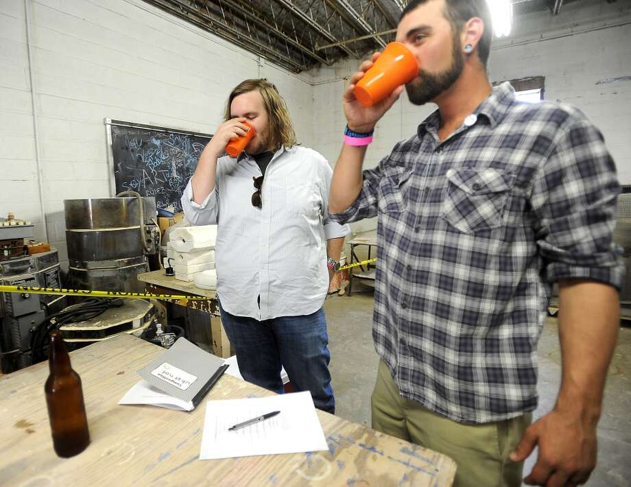 Austin Gillett and Zachary Van Pelt judge a boxtop beer during a home brew contest at The Art Studio in Beaumont, Saturday, October 15, 2011. Tammy McKinley/The Enterprise