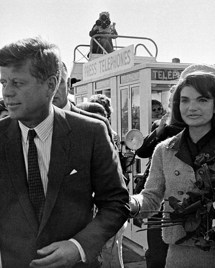 ADVANCE FOR USE SUNDAY, OCT. 20, 2013 AND THEREAFTER - FILE - In this Nov. 22, 1963 file photo, President John F. Kennedy and his wife, Jacqueline Kennedy, arrive at Love Field airport in Dallas, as a television camera, above, follows them. (AP Photo/File) ORG XMIT: NY777 / AP