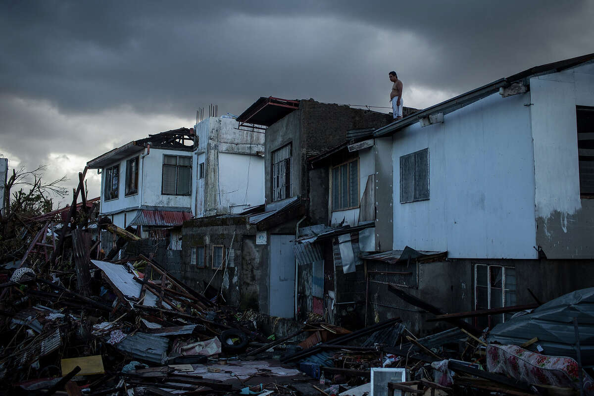 A resident surveys the surrounding damage from a rooftop on November 14, 2013 in Leyte, Philippines. Typhoon Haiyan which ripped through Philippines over the weekend has been described as one of the most powerful typhoons ever to hit land, leaving thousands dead and hundreds of thousands homeless. Countries all over the world have pledged relief aid to help support those affected by the typhoon however damage to the airport and roads have made moving the aid into the most affected areas very difficult. With dead bodies left out in the open air and very limited food, water and shelter, health concerns are growing.