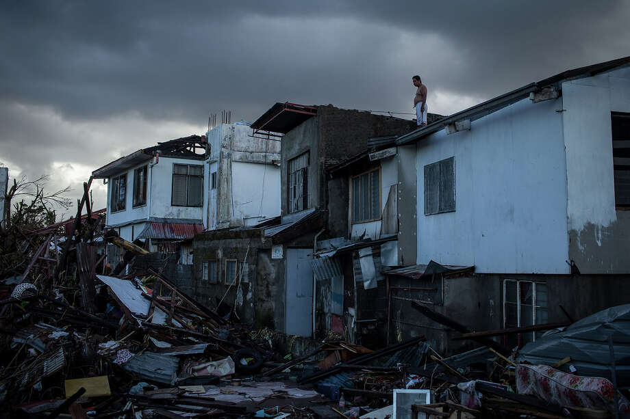 A resident surveys the surrounding damage from a rooftop on November 14, 2013 in Leyte, Philippines. Typhoon Haiyan which ripped through Philippines over the weekend has been described as one of the most powerful typhoons ever to hit land, leaving thousands dead and hundreds of thousands homeless. Countries all over the world have pledged relief aid to help support those affected by the typhoon however damage to the airport and roads have made moving the aid into the most affected areas very difficult. With dead bodies left out in the open air and very limited food, water and shelter, health concerns are growing. Photo: Chris McGrath, Getty Images / 2013 Getty Images
