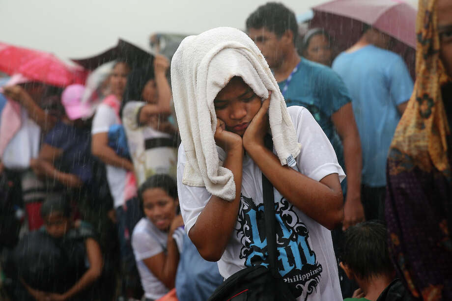 People queue in the rain for a rescue flight at Tacloban Airport on November 14, 2013 in Leyte, Philippines. Typhoon Haiyan which ripped through Philippines over the weekend has been described as one of the most powerful typhoons ever to hit land, leaving thousands dead and hundreds of thousands homeless. Countries all over the world have pledged relief aid to help support those affected by the typhoon, however damage to the airport and roads have made moving the aid into the most affected areas very difficult. With dead bodies left out in the open air and very limited food, water and shelter, health concerns are growing. Photo: Dan Kitwood, Getty Images / 2013 Getty Images