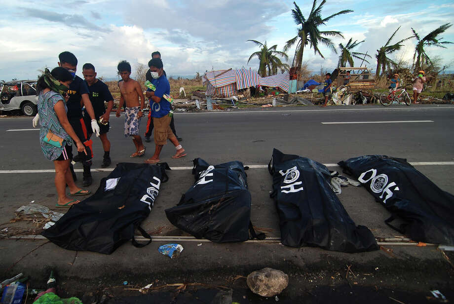Bodies are lined up in body bags on the roadside as members of the fire department retrieve bodies from the rubble in Tacloban City on November 14, 2013 in Leyte, Philippines. Typhoon Haiyan which ripped through Philippines over the weekend has been described as one of the most powerful typhoons ever to hit land, leaving thousands dead and hundreds of thousands homeless. Countries all over the world have pledged relief aid to help support those affected by the typhoon however damage to the airport and roads have made moving the aid into the most affected areas very difficult. With dead bodies left out in the open air and very limited food, water and shelter, health concerns are growing. Photo: Dondi Tawatao, Getty Images / 2013 Getty Images