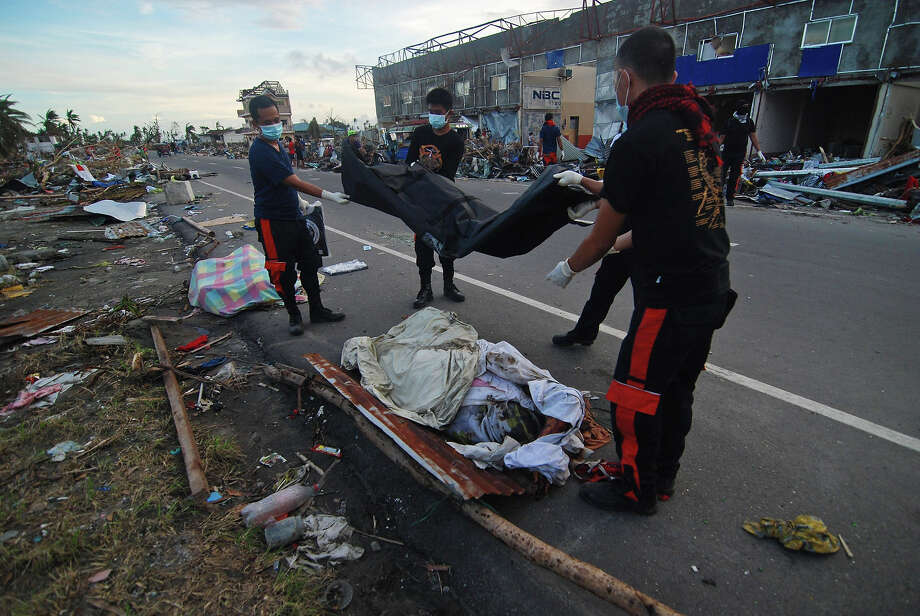 Members of the fire department retrieve bodies from the rubble in Tacloban City on November 14, 2013 in Leyte, Philippines. Typhoon Haiyan which ripped through Philippines over the weekend has been described as one of the most powerful typhoons ever to hit land, leaving thousands dead and hundreds of thousands homeless. Countries all over the world have pledged relief aid to help support those affected by the typhoon however damage to the airport and roads have made moving the aid into the most affected areas very difficult. With dead bodies left out in the open air and very limited food, water and shelter, health concerns are growing. Photo: Dondi Tawatao, Getty Images / 2013 Getty Images