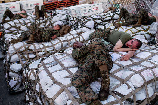 US military personel sleep on aid shipments at Tacloban Airport on November 15, 2013 in Leyte, Philippines. Typhoon Haiyan which ripped through Philippines over the weekend has been described as one of the most powerful typhoons ever to hit land, leaving thousands dead and hundreds of thousands homeless. Countries all over the world have pledged relief aid to help support those affected by the typhoon however damage to the airport and roads have made moving the aid into the most affected areas very difficult. With dead bodies left out in the open air and very limited food, water and shelter, health concerns are growing. Photo: Chris McGrath, Getty Images / 2013 Getty Images