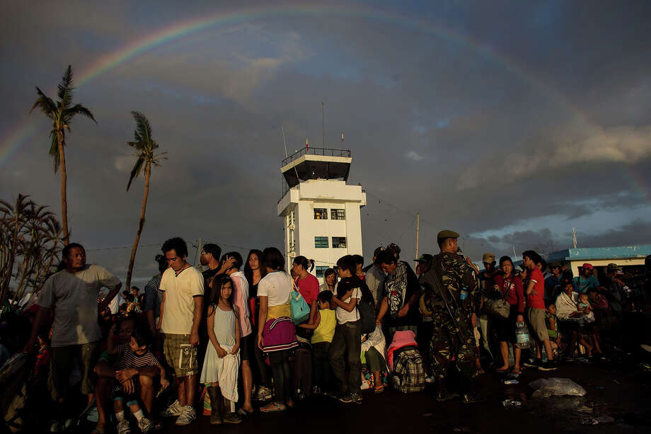 People wait  for flights out of Tacloban Airport in the early hours of the morning on November 15, 2013 in Leyte, Philippines. Typhoon Haiyan which ripped through Philippines over the weekend has been described as one of the most powerful typhoons ever to hit land, leaving thousands dead and hundreds of thousands homeless. Countries all over the world have pledged relief aid to help support those affected by the typhoon however damage to the airport and roads have made moving the aid into the most affected areas very difficult. With dead bodies left out in the open air and very limited food, water and shelter, health concerns are growing. Photo: Chris McGrath, Getty Images / 2013 Getty Images