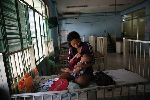 Joanne Vernen cares for her 3-month-old son Dwayne who is suffering from dehydration in Tacloban Hospital on November 15, 2013 in Leyte, Philippines. Typhoon Haiyan which ripped through Philippines over the weekend has been described as one of the most powerful typhoons ever to hit land, leaving thousands dead and hundreds of thousands homeless. Countries all over the world have pledged relief aid to help support those affected by the typhoon, however damage to the airport and roads have made moving the aid into the most affected areas very difficult. With dead bodies left out in the open air and very limited food, water and shelter, health concerns are growing. Photo: Dan Kitwood, Getty Images / 2013 Getty Images