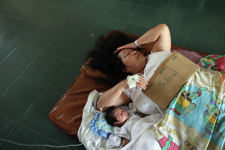 A woman and her new born baby lay on the floor in Tacloban Hospital on November 15, 2013 in Leyte, Philippines. Typhoon Haiyan which ripped through Philippines over the weekend has been described as one of the most powerful typhoons ever to hit land, leaving thousands dead and hundreds of thousands homeless. Countries all over the world have pledged relief aid to help support those affected by the typhoon, however damage to the airport and roads have made moving the aid into the most affected areas very difficult. With dead bodies left out in the open air and very limited food, water and shelter, health concerns are growing. Photo: Dan Kitwood, Getty Images / 2013 Getty Images
