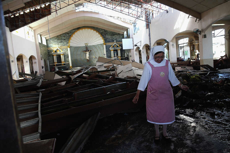 Sister Mary James wades through mud inside the destroyed St Joseph Church on November 15, 2013 in Tacloban, Philippines. Typhoon Haiyan which ripped through Philippines over the weekend has been described as one of the most powerful typhoons ever to hit land, leaving thousands dead and hundreds of thousands homeless. Countries all over the world have pledged relief aid to help support those affected by the typhoon, however damage to the airport and roads have made moving the aid into the most affected areas very difficult. With dead bodies left out in the open air and very limited food, water and shelter, health concerns are growing. Photo: Dan Kitwood, Getty Images / 2013 Getty Images