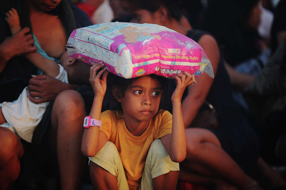 A young child waits for a flight out of Tacloban Airport in the early hours of the morning on November 15, 2013 in Leyte, Philippines. Typhoon Haiyan which ripped through Philippines over the weekend has been described as one of the most powerful typhoons ever to hit land, leaving thousands dead and hundreds of thousands homeless. Countries all over the world have pledged relief aid to help support those affected by the typhoon, however damage to the airport and roads have made moving the aid into the most affected areas very difficult. With dead bodies left out in the open air and very limited food, water and shelter, health concerns are growing. Photo: Dan Kitwood, Getty Images / 2013 Getty Images