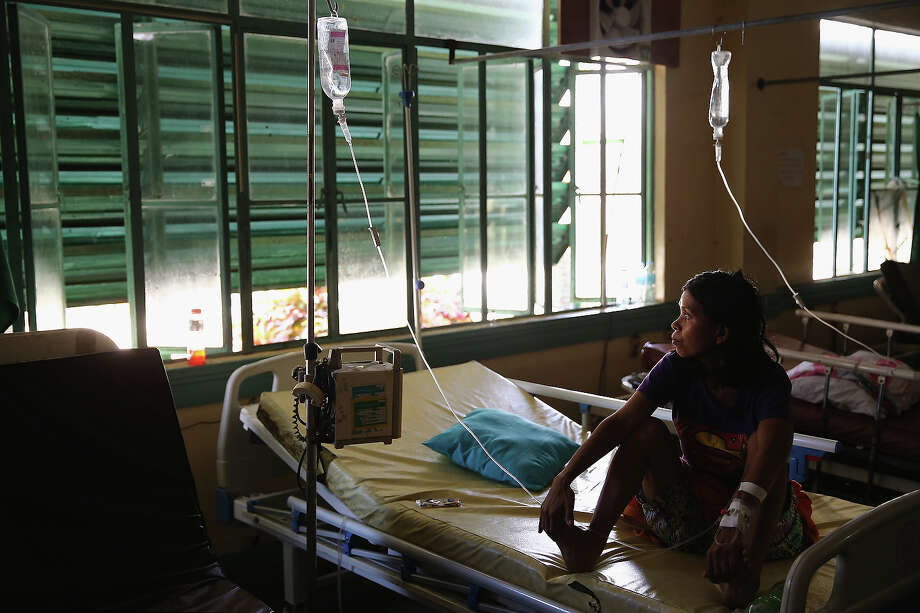 A woman waits to be treated in Tacloban Hospital on November 15, 2013 in Leyte, Philippines. Typhoon Haiyan which ripped through Philippines over the weekend has been described as one of the most powerful typhoons ever to hit land, leaving thousands dead and hundreds of thousands homeless. Countries all over the world have pledged relief aid to help support those affected by the typhoon, however damage to the airport and roads have made moving the aid into the most affected areas very difficult. With dead bodies left out in the open air and very limited food, water and shelter, health concerns are growing. Photo: Dan Kitwood, Getty Images / 2013 Getty Images