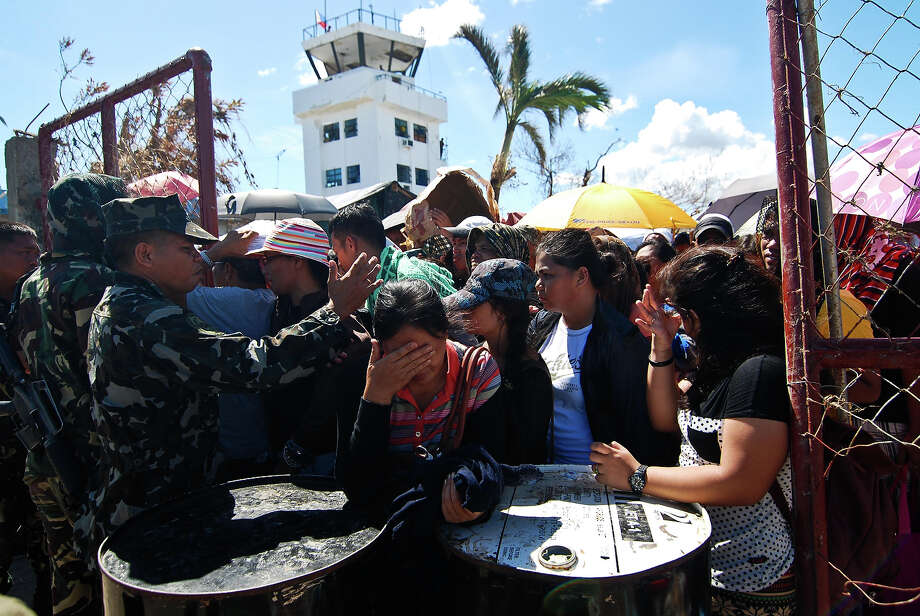 Survivors wait for a military plane that will carry them to Manila at Tacloban airport on November 15, 2013 in Leyte, Philippines. Typhoon Haiyan which ripped through Philippines over the weekend has been described as one of the most powerful typhoons ever to hit land, leaving thousands dead and hundreds of thousands homeless. Countries all over the world have pledged relief aid to help support those affected by the typhoon, however damage to the airport and roads have made moving the aid into the most affected areas very difficult. With dead bodies left out in the open air and very limited food, water and shelter, health concerns are growing. Photo: Dondi Tawatao, Getty Images / 2013 Getty Images