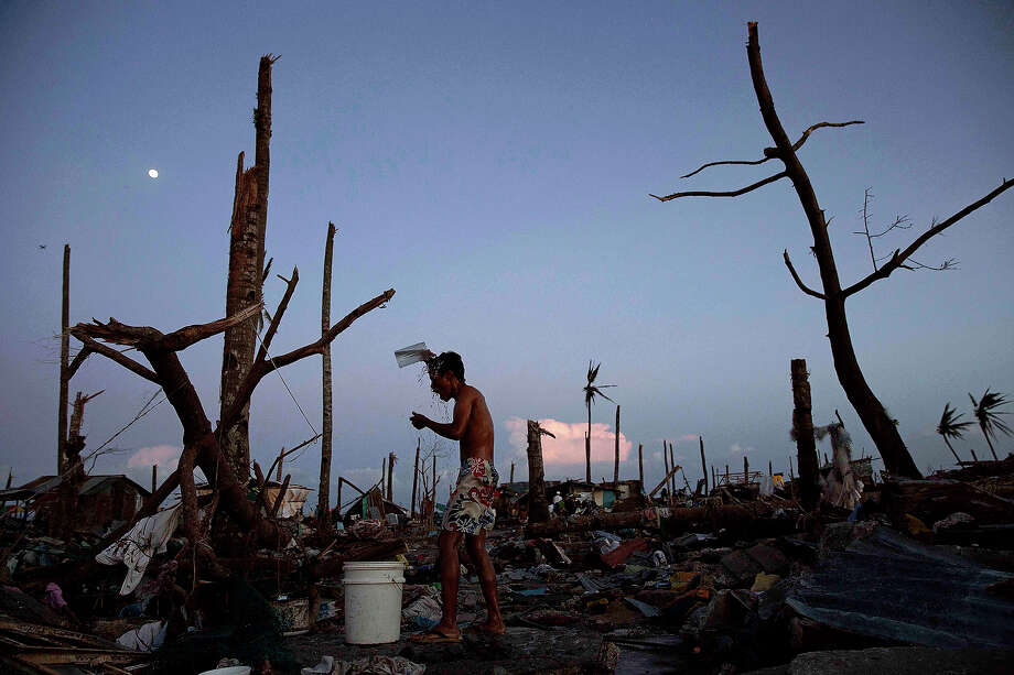 A young man bathes in the rubble of his destroyed house in the devastated town of Tanuan, south of Tacloban on November 15, 2013 in Philippines. Typhoon Haiyan ripped through Philippines over the weekend and has been described as one of the most powerful typhoons ever to hit land, leaving thousands dead and hundreds of thousands homeless. Countries all over the world have pledged relief aid to help support those affected by the typhoon, however damage to the airport and roads have made moving the aid into the most affected areas very difficult. With dead bodies left out in the open air and very limited food, water and shelter, health concerns are growing. Photo: Kevin Frayer, Getty Images / 2013 Getty Images