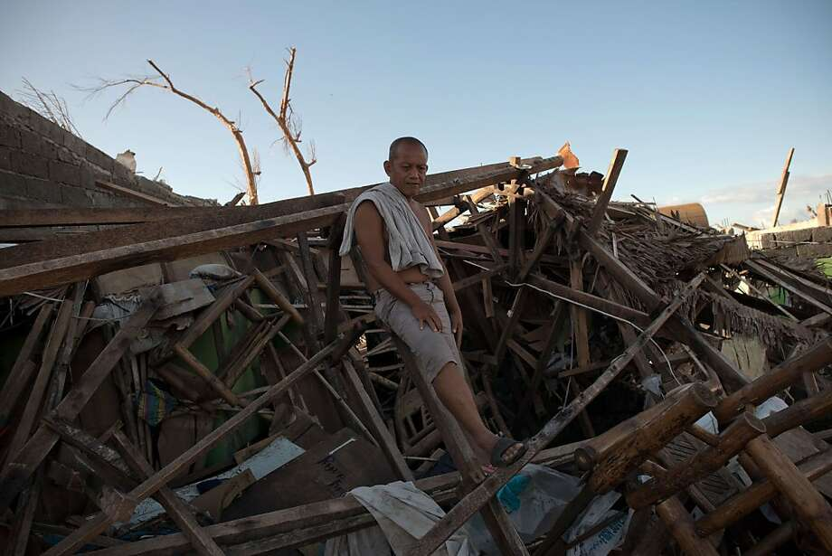 A typhoon survivor stands in the debris of his destroyed house in Palo, on the outskirts of Tacloban. Typhoon Haiyan tore through the central part of the Philippines. Photo: Nicolas Asfouri, AFP/Getty Images