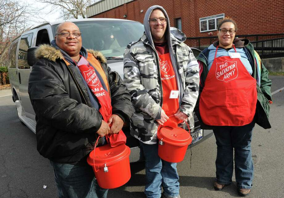 From left, Salvation Army volunteers Ricardo Hamlett, Edward Arusti and Loulonnie Raybine, all of Albany, get ready to board a van and head to different locations for the 2013 Annual Bell Ringing Campaign on Friday, Nov. 15, 2013 in Albany, N.Y.  (Lori Van Buren / Times Union) Photo: Lori Van Buren / 00024652A