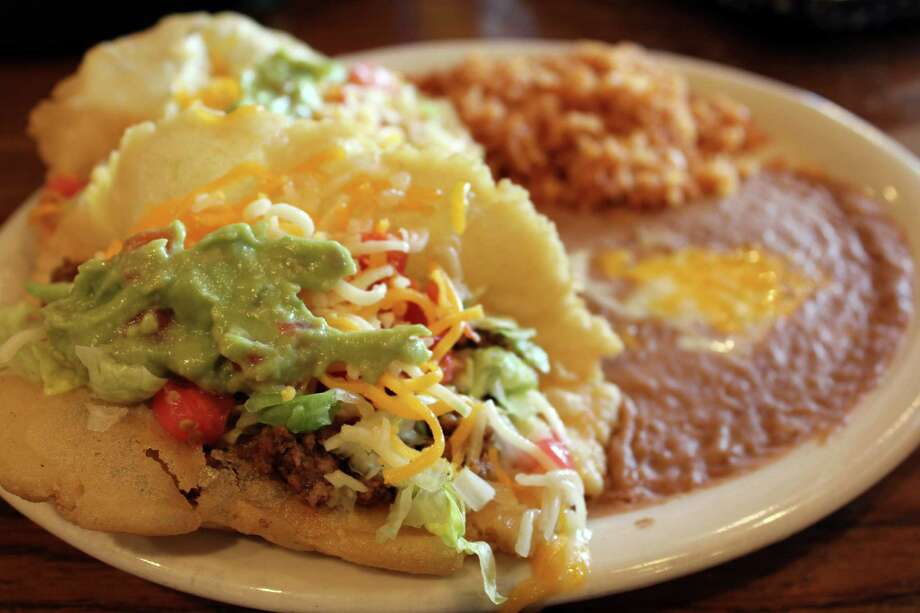 A plate of two puffy tacos, one beef and one chicken topped with lettuce, tomatoes and cheese, is served with rice, refried beans and tortillas.  Photo: Jennifer McInnis, San Antonio Express-News / San Antonio Express-News