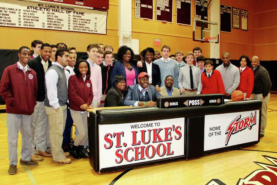 Surrounded by family and friends, St. Luke's Ami Lakoju signs his Letter of Intent to play basketball at Fairfield University. Contributed photo by Desiree Smock. Photo: Contributed Photo / New Canaan News
