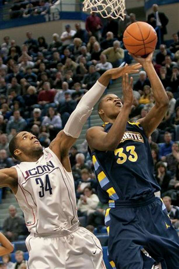 Marquette's Jimmy Butler, right, shoots the ball past Connecticut's Alex Oriakhi during the second half of Marquette's 70-68 win in an NCAA college basketball game in Hartford, Conn., on Saturday, Jan. 30, 2010. Photo: AP/Thomas Cain