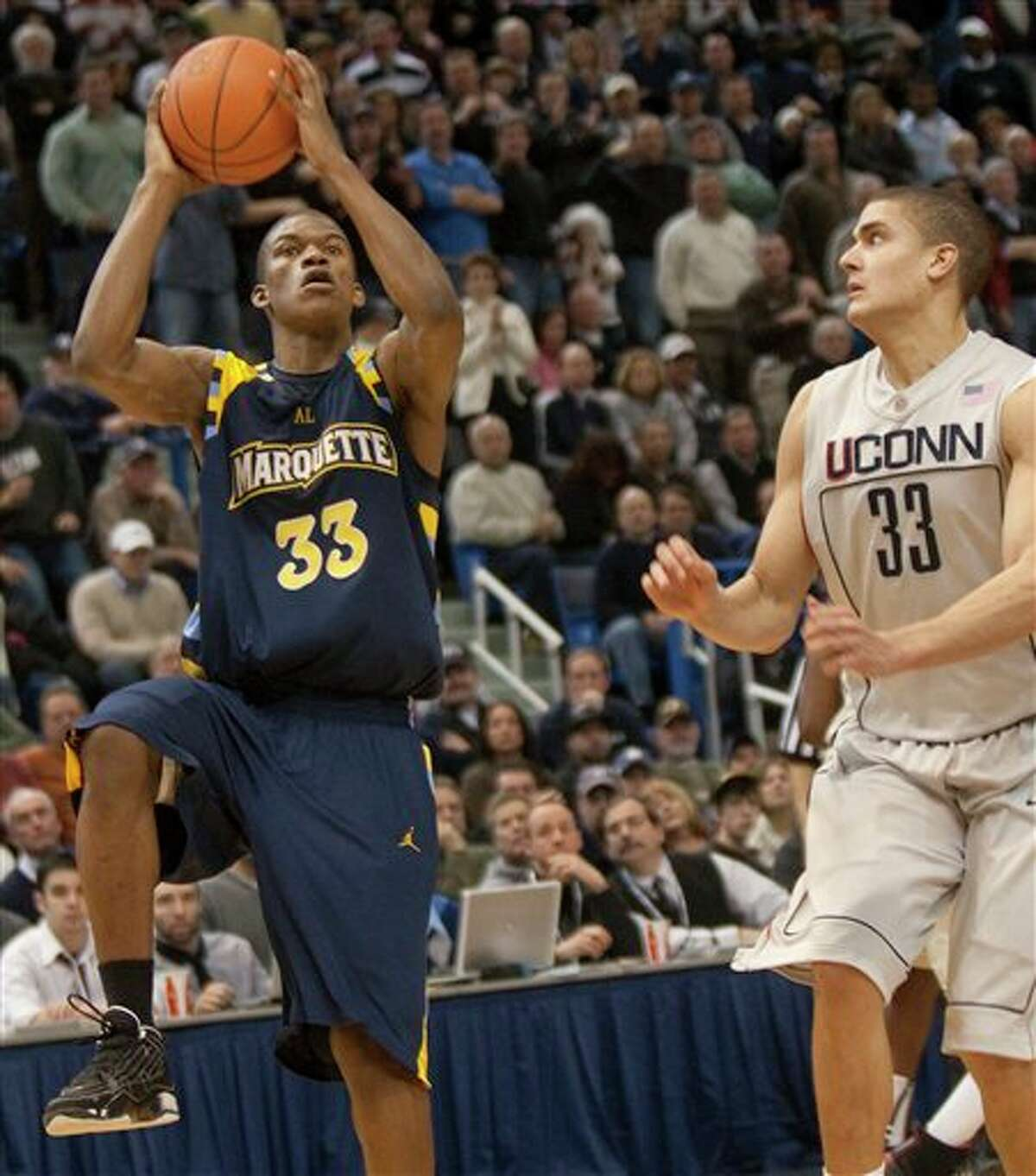 Marquette's Jimmy Butler, left, shoots the game-winning basket as Connecticut's Gavin Edwards, right, defends during the closing seconds of the second half of Marquette's 70-68 win in an NCAA college basketball game in Hartford, Conn., on Saturday, Jan. 30, 2010.