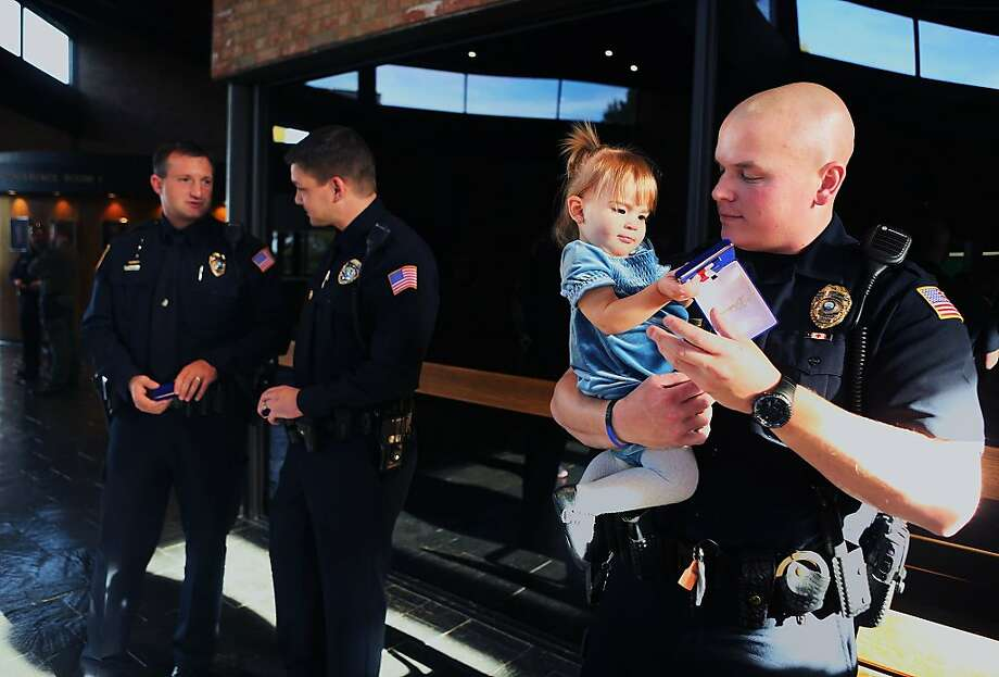Her hero:Officer Josh Schultz lets his daughter, Ella, play with his Life Saving Award, which he received 