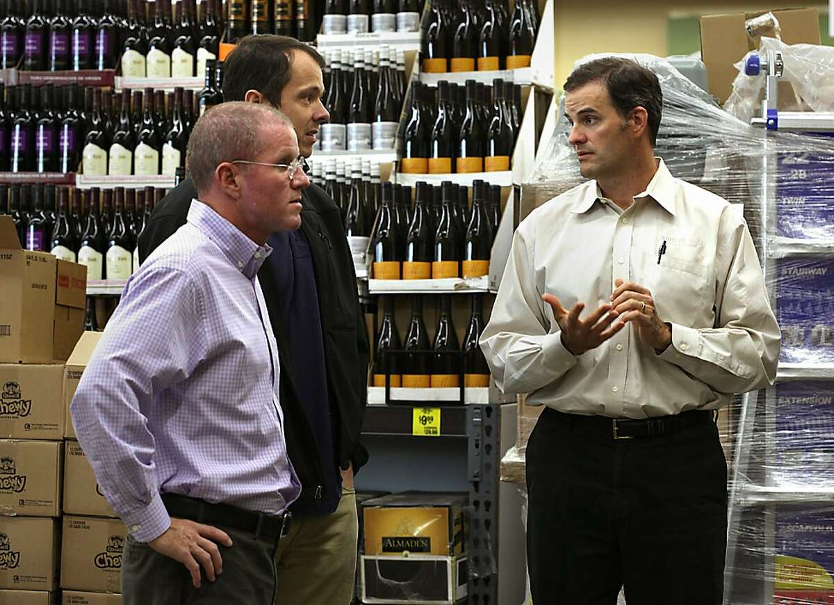 Co-CEO's Eric Lindberg Jr. (right) and MacGregor Read (front left) talk with store manager Travis Dawson (back left)) in the wine section of the new Grocery Outlet under construction on Geary St. in San Francisco, California, on Monday, November 11, 2013. This will be the 202nd Grocery Outlet store which will be opening next week.