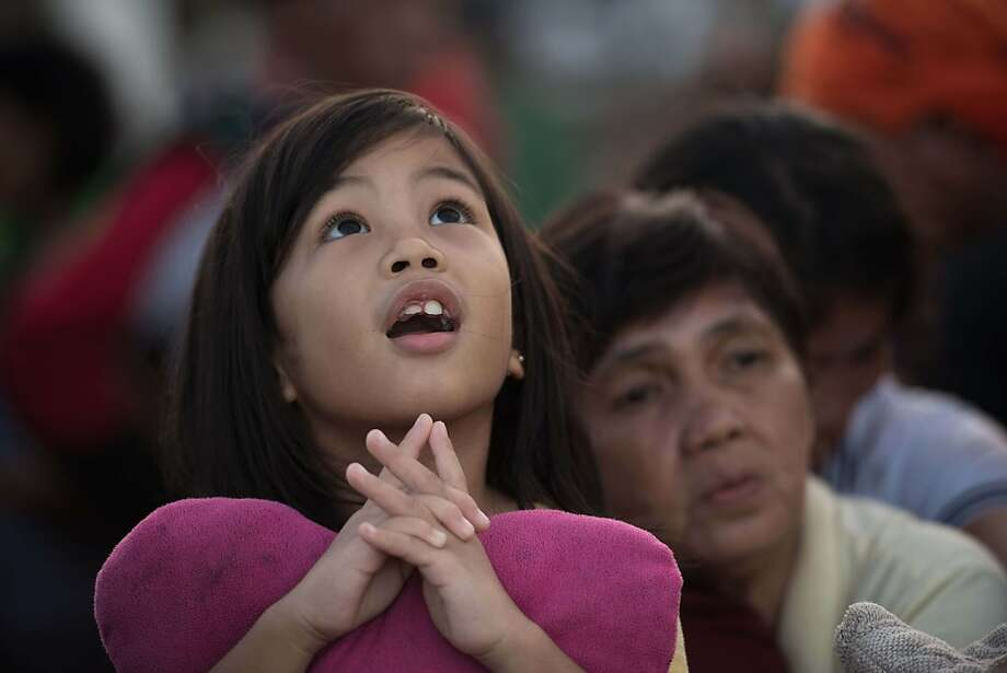 Finally!A young girl watches army helicopters land as she waits in line with other typhoon survivors for a chance to 