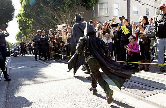Batman and five year old Miles Scott as Batkid are off and running to their next adventure after the rescue of a damsel in distress along the Hyde Street cable car line in San Francisco Ca., Friday Nov. 15, 2013. Photo: Michael Macor, The Chronicle
