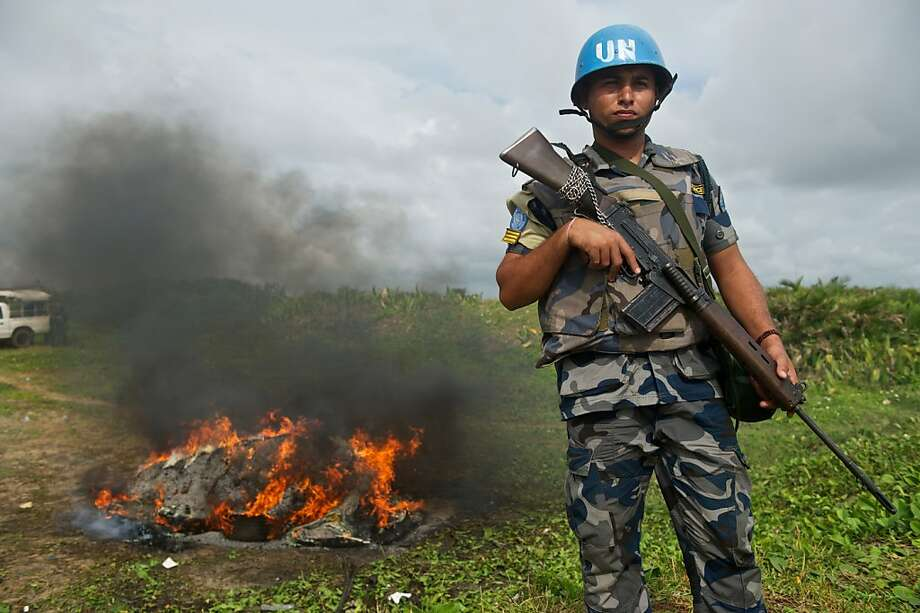 Motorcade marijuana bust: U.N. peacekeeper Yubaras Puri stands guard as Liberian Drug Enforcement 