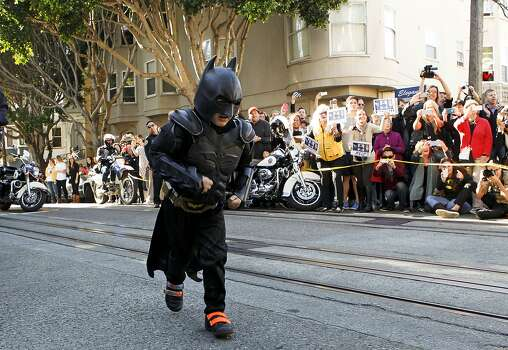 Miles as Batkid runs to the scene of a report of a damsel in distress along the Hyde Street cable car line in San Francisco Ca., on Friday Nov. 15, 2013.   Five year old Miles from Tulelake in Siskiyou County loves superheroes and Batman in particular. After battling leukemia since he was a year old Miles will fulfill his dream of becoming Batkid being swept around the city performing superhero feats from rescuing a damsel in distress to thwarting a bank robbery and even chasing down the Penguin through AT&T Park Photo: Michael Macor, The Chronicle