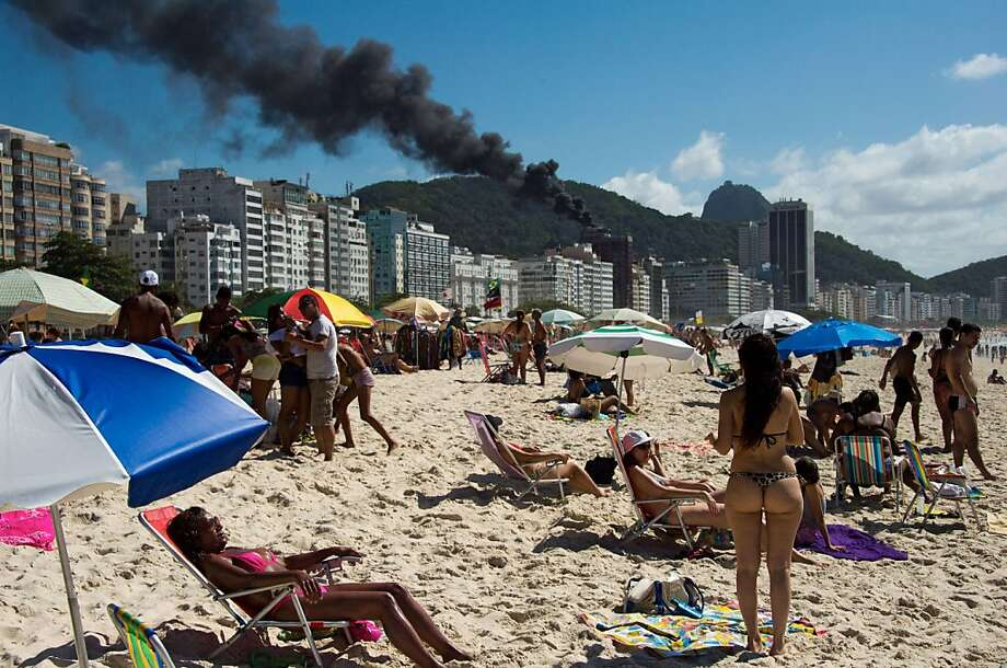 Beach blaze blase:No one on Copacabana beach in Rio de Janeiro seems too concerned about an apparent fire at the Porto Bay Rio International Hotel. Photo: Christophe Simon, AFP/Getty Images