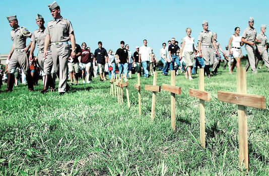 Families and friends walk by 12 crosses representing the victims killed in the collapse of Texas A&M Bonfire on the Texas A&M Campus during a memorial groundbreaking ceremony, July 19, 2003, in College Station. Photo: PATRIC SCHNEIDER, AP / BRYAN EAGLE