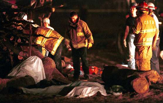 Members of the College Station, Texas fire department stand near the covered bodies of two of the people who died early on the morning or Nov. 18, 1999, when a 40-foot pyramid of logs assembled for Texas A&M University's traditional pregame bonfire collapsed. Sixty to 70 students were on top of the logs when the accident happened at 2:30 a.m. in a field on the northeast corner of the campus, according to university officials. Photo: SALLIE TURNER, AP / THE BATTALION