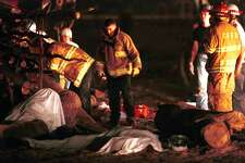 Members of the College Station (Texas) Fire department stand near the covered bodies of two of the four people who died early Thursday morning, Nov. 18, 1999, when a 40-foot pyramid of logs assembled for Texas A&M University's traditional pregame bonfire collapsed. Sixty to 70 students were on top of the logs when the accident happened at 2:30 a.m. in a field on the northeast corner of the campus, according to university officials.