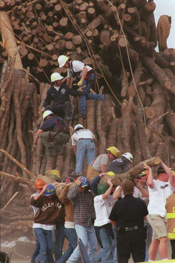 Emergency personnel use wire cutters to loosen logs tied to the collapsed stack of the A&M Bonfire. Students and rescue workers remove the logs to help in the search for victims. Photo: Steve Ueckert, Houston Chronicle / Houston Chronicle