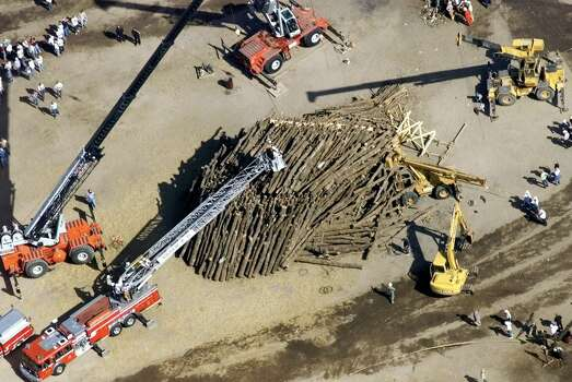 Fire trucks, cranes and other heavy equipment involved in search and rescue surround and probe the pile of logs that was being constructed for Texas A&M's traditional football bonfire at Texas A&M University.  Photo: DOUG SEHRES, AP / SAN ANTONIO EXPRESS-NEWS
