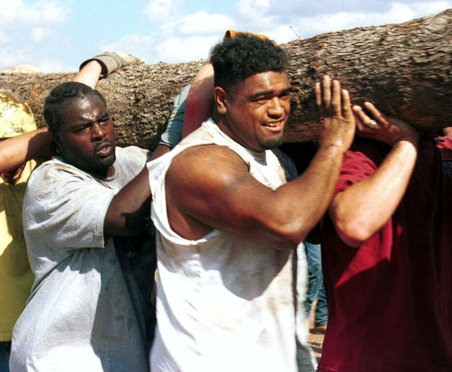 Texas A&M football players, D'Andre 'Tiki' Hardeman, left, and Semisi Heimuli, help carry a log away from the collapsed bonfire, Nov. 18, 1999 at the Texas A&M bonfire site on Texas A&M University in College Station. Photo: JP BEATO, AP / THE BATTALION