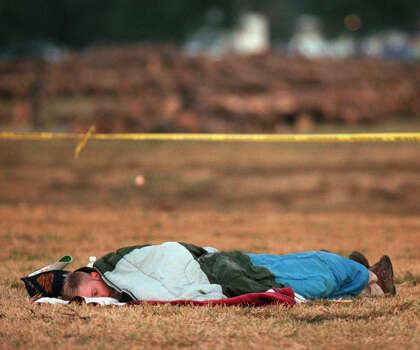 Texas A&M students Mac Nabours and Amanda Cornett (right, under covers) sleep Nov. 19, 1999, next to the site where a bonfire under construction collapsed Thursday in College Station. Photo: Smiley N. Pool, Houston Chronicle / Houston Chronicle