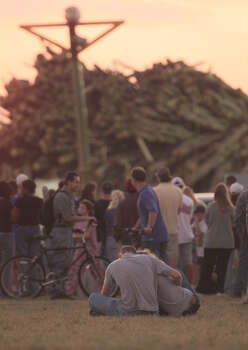 Students watch as emergency workers continue into the evening removing logs from the bonfire accident site. Photo: SMILEY N. POOL, Houston Chronicle / Houston Chronicle