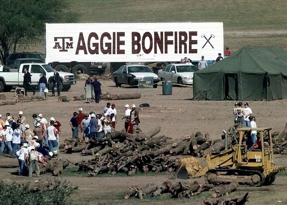 Texas A&M students move logs that were extracted from the bonfire stack in College Station.  At least nine students were killed and more than 25 injured when the 40-foot structure collapsed in the early morning hours. Photo: PAT SULLIVAN, AP / AP