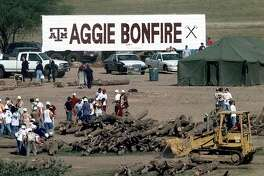 Texas A&M students move logs that were extracted from the bonfire stack Thursday, Nov. 18, 1999, in College Station, Texas.  At least nine students were killed and more than 25 injured when the 40-foot structure collapsed in the early morning hours.