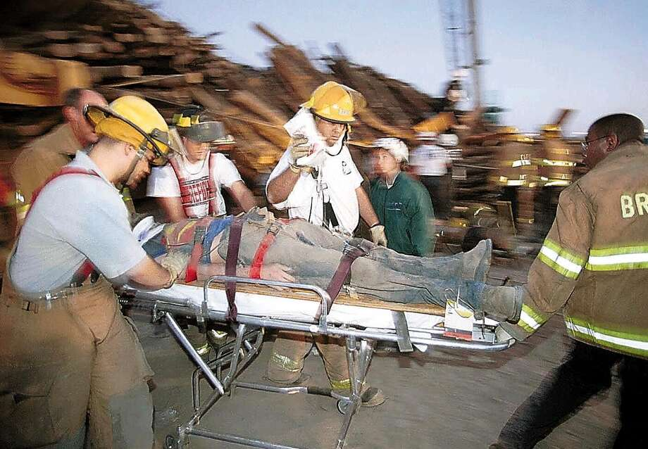 Emergency workers rush a student who was trapped for hours under a stack of logs that collapsed while being prepared for a pre-football game bonfire early on Nov. 18, 1999 at Texas A&M University in College Station. Photo: DAVE MCDERMAND, AP / BRYAN-COLLEGE STATION EAGLE