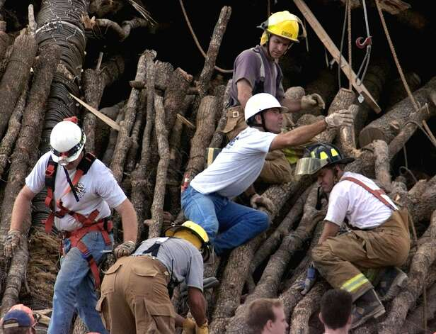 Rescuers work to free students trapped beneath the pile of logs that were being stacked for the traditional homecoming bonfire at Texas A&M on Nov. 18, 1999, in College Station Photo: ERIC GAY, AP / AP