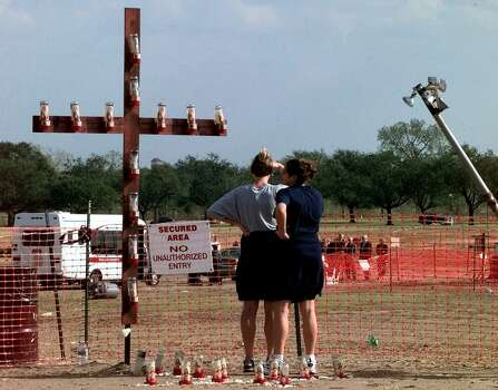 Two Texas A&M students visit a memorial crucifix at the site of last month's tragedy as members of the Special Commission on the 1999 Bonfire, background, inspect the site Dec. 3, 1999, in College Station. The cross holds 12 candles for the 12 victims of the collapse. Photo: PAT SULLIVAN, AP / AP