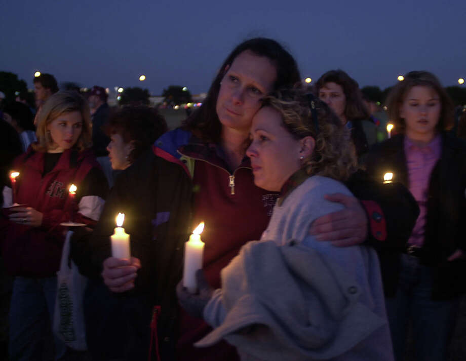 Wendy Jones, right, class of '79, gets a hug from Pam Watson,  on the Texas A&M campus during a candlelight vigil Nov. 25, 1999 at the site where 12  died in the bonfire collapse. (Smiley N. Pool/Chronicle) Photo: SMILEY N. POOL, Houston Chronicle / Houston Chronicle