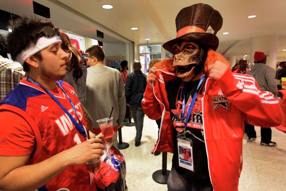 Albert Morena, left,  of Houston waits for Justin Arriazola of Houston to put on his new All-Star jacket after they brought souvenirs during the NBA All-Star Game at the Toyota Center on Sunday, Feb. 17, 2013, in Houston. Both are members of the Houston Rockets Red Rowdies fan group and Justin wears the monkey mask to the Rockets game. ( Melissa Phillip / Houston Chronicle ) Photo: Melissa Phillip, Chronicle / © 2013  Houston Chronicle